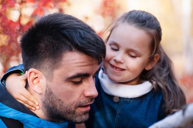 Nahaufnahme von mann und mädchen familienporträt fantastischer dunkelhaariger mann und lächelndes kleines mädchen in blauer jacke ...