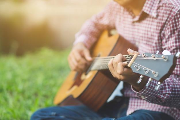 Nahaufnahme von mannhänden, die auf akustischer gitarre spielen Premium Fotos