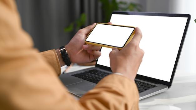 Nahaufnahme von mannhänden, die ein horizontales mobiltelefon halten, während er im home office vor seinem computertablett sitzt.