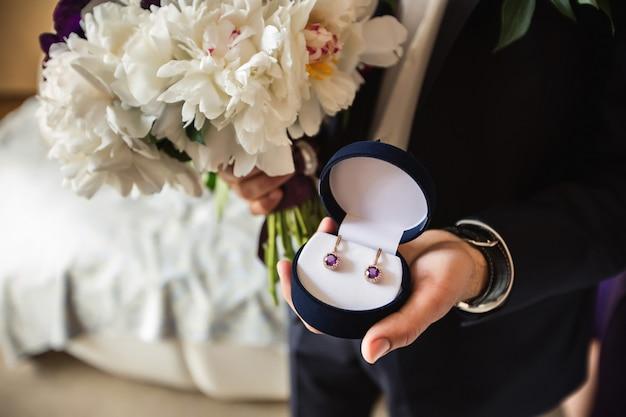 Nahaufnahme von mannhänden, die geschenkbox mit luxusschmuck halten