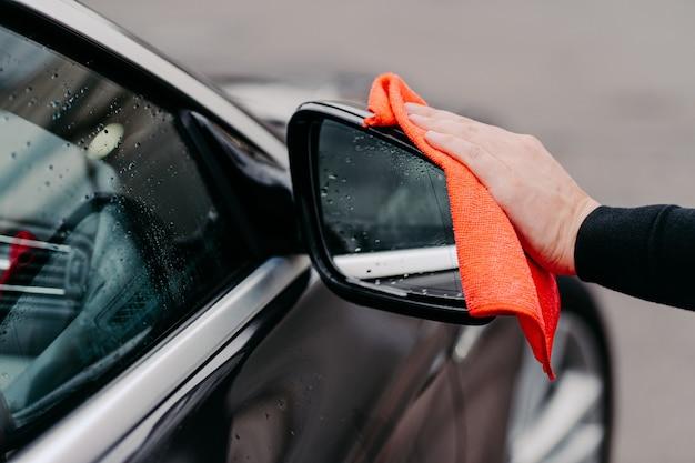Nahaufnahme von mans hand, die wasser auf schwarzem auto mit mikrofasertuch abwischt. konzentrieren sie sich auf den automatischen seitenspiegel. transporation selbstbedienung