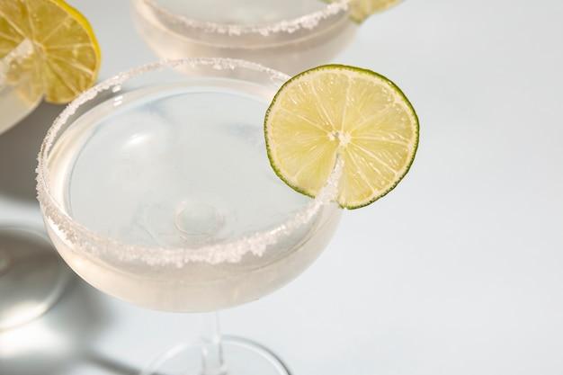 Nahaufnahme von margarita im glas mit kalk auf weißem schreibtisch