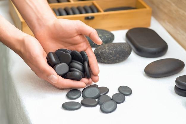 Nahaufnahme von massage schwarzen steinen in den händen des mannes.