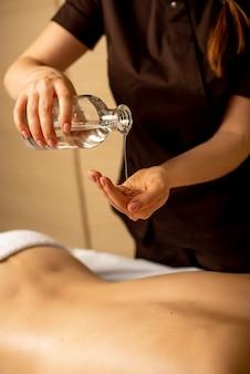 Nahaufnahme von masseurhänden, die aromaöl auf den rücken der frau gießen