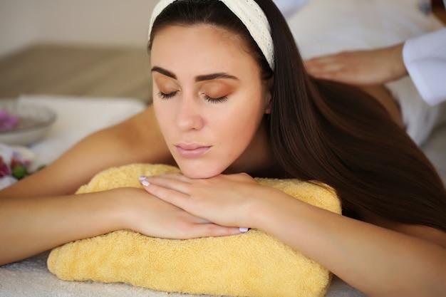 Nahaufnahme von masseurs händen, die den rücken eines kunden massieren