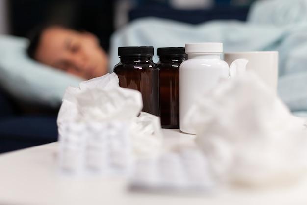 Nahaufnahme von medikamenten für kranke frau, die auf dem sofa schläft