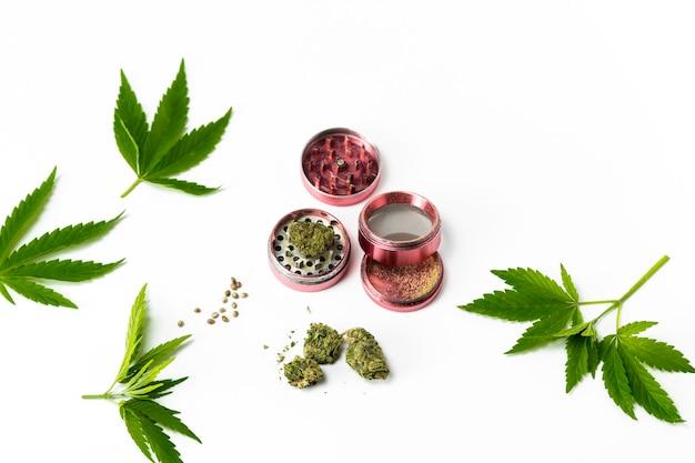 Nahaufnahme von medizinischen marihuanaknospen hanfsamenblätter und mühle auf weißem hintergrund