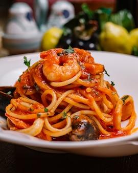 Nahaufnahme von meeresfrüchtespaghetti mit muscheln garnelen tomatensauce und petersilie