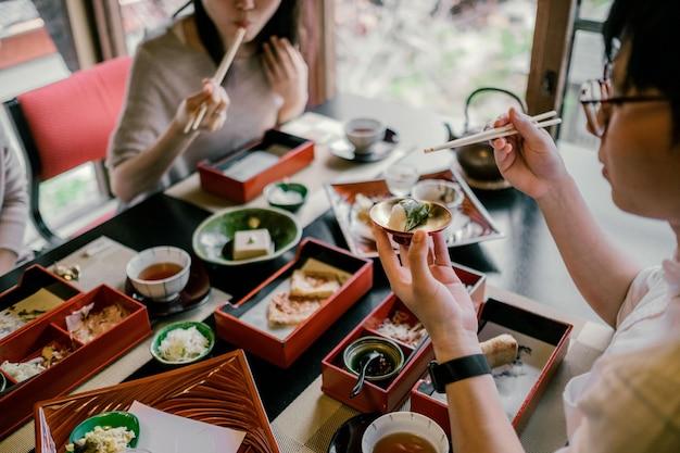 Nahaufnahme von menschen, die mit stäbchen essen
