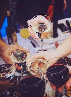 Nahaufnahme von menschen, die über dem restauranttisch anstoßen. trinken von toasts bei einem bankett. feier mit getränken und speisen bei einer dinnerparty. männer und frauen feiern eine veranstaltung. ein trinkstoast