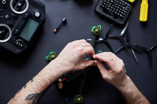Nahaufnahme von menschenhänden, die eine fpv-drohne aus teilen zusammenbauen, mit werkzeugen, hochgeschwindigkeits-rennquadcopter für den flug vorbereiten. reparieren sie die drohne vor dem training.