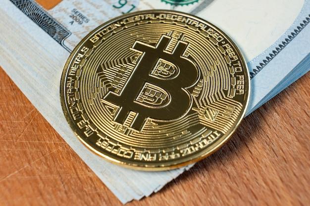 Nahaufnahme von metall glänzenden bitcoin-kryptowährungsmünze auf us-dollar-scheine. elektronisches dezentrales geldkonzept.