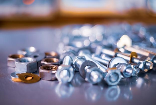 Nahaufnahme von metallchromschrauben und -muttern in chaotischer reihenfolge. hintergrundkonzept für verbindungselemente und konstruktionsthemen. reparatur- und ersatzteilkonzept