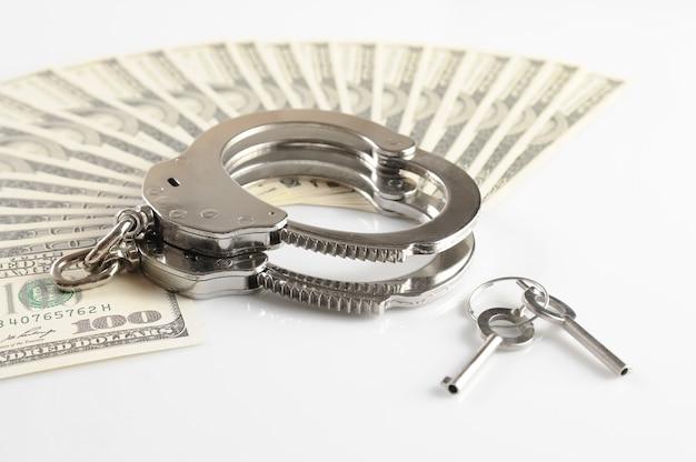 Nahaufnahme von metallhandschellen, schlüsseln und geldpackung der amerikanischen dollar lokalisiert über weißem hintergrund. illegale geldverdienungs-, bestechungs- und korruptionsserien
