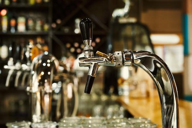 Nahaufnahme von metallischen bierzapfstellen an der bartheke. konzept der modernen bar, brauereiausrüstung.