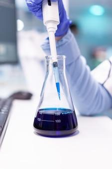 Nahaufnahme von mikropipette, die in reagenzglas für wissenschaftliches experiment eintaucht