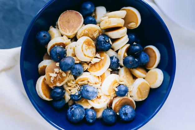 Nahaufnahme von mini-pfannkuchen-müsli, mini-pfannkuchen in einer dunkelblauen schüssel mit ahornsirup-honig mit blaubeeren. lebensmittelhintergrund.