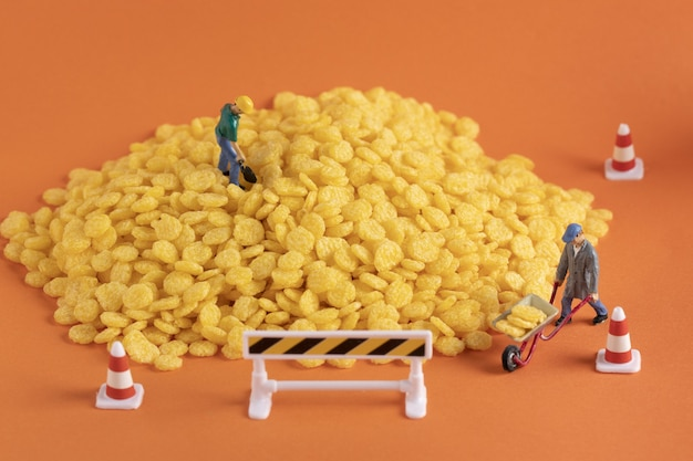 Nahaufnahme von miniatur-arbeitsfiguren auf einem maishaufen auf orangefarbener oberfläche