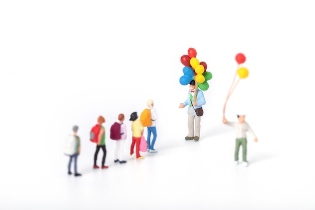 Nahaufnahme von miniaturfiguren von studenten, die sich einem mann nähern, der luftballons hält