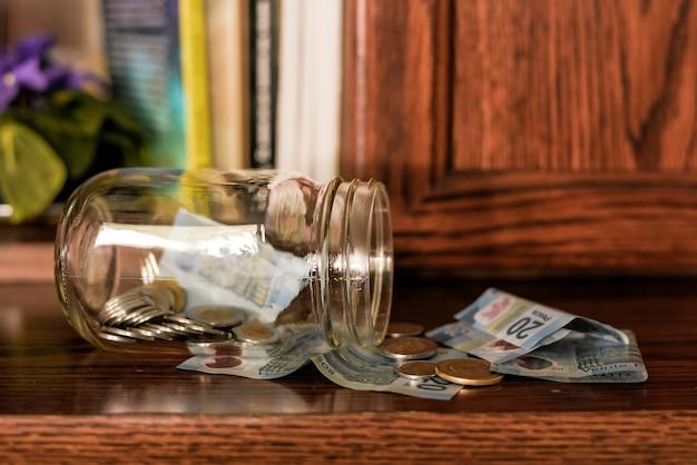 Nahaufnahme von münzen in einem glas auf dem tisch mit pesos unter den lichtern