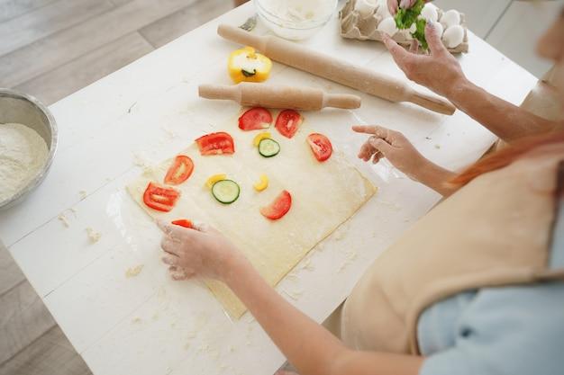 Nahaufnahme von mutter und tochter, die vegane pizza in der küche zubereiten