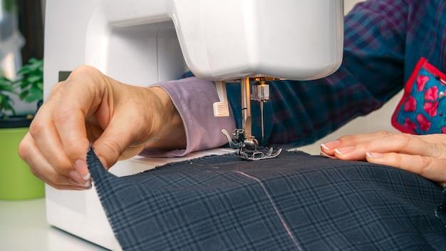 Nahaufnahme von näherinnen, die mit kleidungsstücken auf einer nähmaschine arbeiten