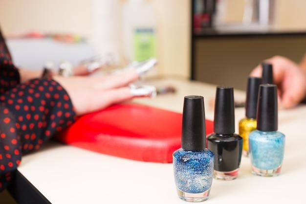 Nahaufnahme von nagellackflaschen in verschiedenen farben auf dem tisch im spa mit händen der weiblichen kundin, die während der spa-maniküre in folienverpackungen im hintergrund gewickelt sind