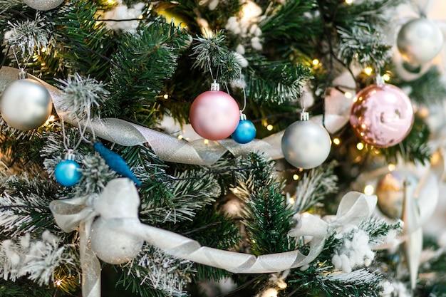 Nahaufnahme von neujahrsbaum mit verschiedenen ornamenten. festlicher weihnachtshintergrund