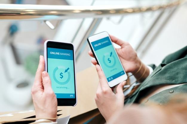 Nahaufnahme von nicht erkennbaren frauen, die mobiltelefone verwenden, während sie geld online überweisen
