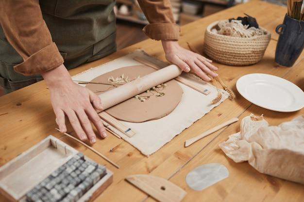 Nahaufnahme von nicht erkennbaren handwerkern, die keramik mit pflanzenabdruck auf holztisch in der töpferwerkstatt herstellen, kopierraum