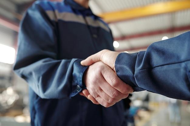 Nahaufnahme von nicht erkennbaren ingenieuren in blauer arbeitskleidung, die in der fabrik stehen und beim abschluss des geschäfts handschlag machen