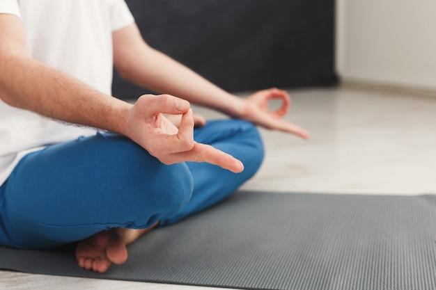 Nahaufnahme von nicht erkennbaren mannhänden, meditierend, sitzend in lotuspose auf matte, kopienraum