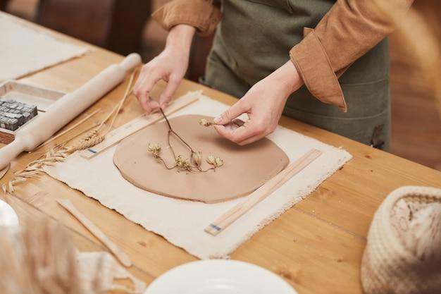 Nahaufnahme von nicht erkennbaren weiblichen handwerkern, die pflanzenabdruckkeramik auf holztisch in der töpferwerkstatt herstellen, kopierraum