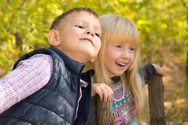 Nahaufnahme von niedlichen weißen kleinen kindern, die im herbstpark mit grünem baumhintergrund genießen.