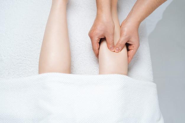 Nahaufnahme von oben auf den männlichen masseur, der der jungen frau, die auf dem massagetisch liegt, den unteren teil des beins massiert