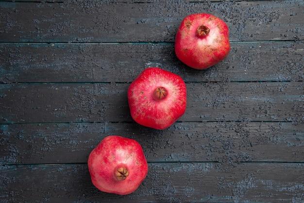 Nahaufnahme von oben drei reife granatäpfel granatäpfel in der mitte des grauen holztisches