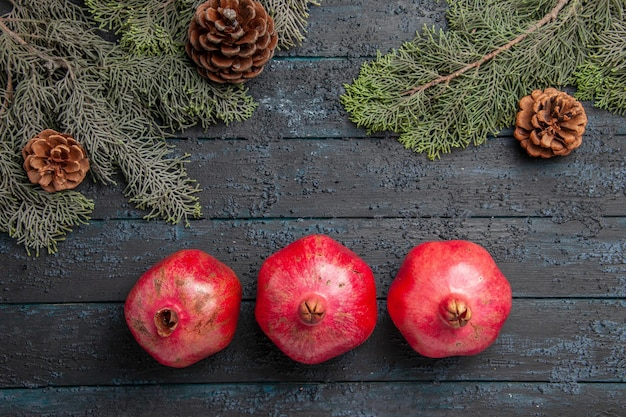 Nahaufnahme von oben drei rote granatäpfel drei reife granatäpfel neben fichtenzweigen mit zapfen in der tischmitte
