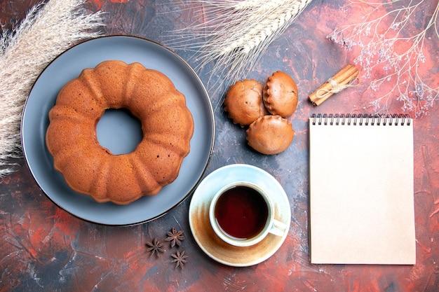 Nahaufnahme von oben ein appetitlicher kuchen kuchen cupcakes eine tasse tee zimt weißes notizbuch weizenähren