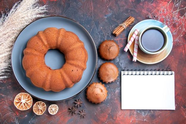 Nahaufnahme von oben ein appetitlicher kuchen leckerer kuchen cupcakes eine tasse tee zitrone zimt notizbuch