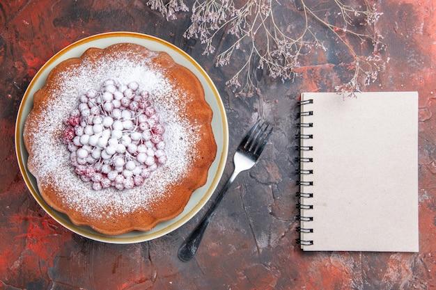 Nahaufnahme von oben ein kuchen ein gabelweißes notizbuch neben dem appetitlichen kuchen mit roten johannisbeeren