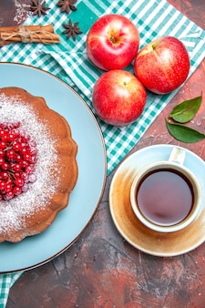 Nahaufnahme von oben ein kuchen ein kuchen mit beeren äpfel eine tasse tee zimtstangen sternanis