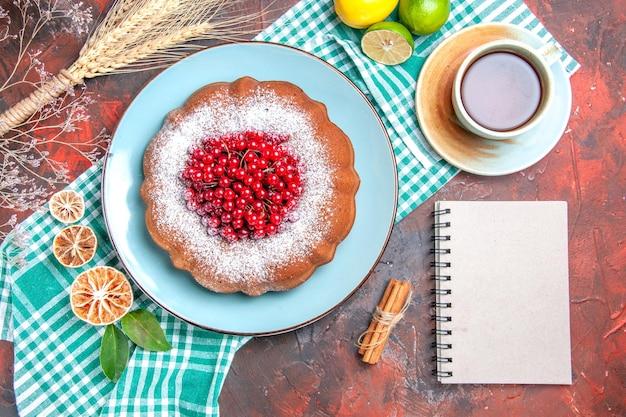 Nahaufnahme von oben ein kuchen ein kuchen mit beeren limetten auf der tischdecke eine tasse tee weißes notizbuch