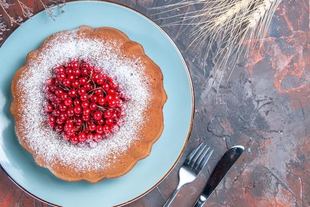 Nahaufnahme von oben ein kuchen ein kuchen mit roten johannisbeeren auf dem teller weizenähren messer und gabel