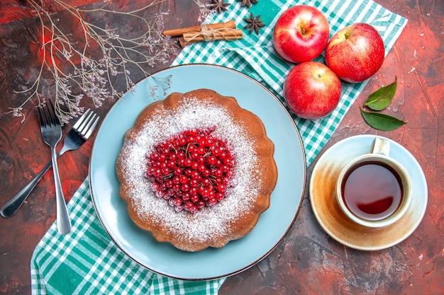 Nahaufnahme von oben ein kuchen ein kuchen mit roten johannisbeeren drei äpfel eine tasse tee gabelten zimt