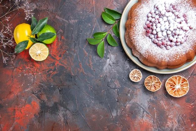 Nahaufnahme von oben ein kuchen ein kuchen mit roten johannisbeeren zitrusfrüchte blätter zweige