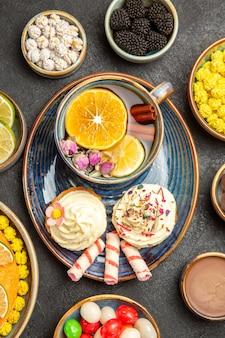 Nahaufnahme von oben eine tasse kräutertee ein teller cupcakes mit sahne eine tasse kräutertee mit zitrone und süßigkeiten neben den schalen mit beeren zitrusfrüchte weiße bonbons auf dem dunklen tisch