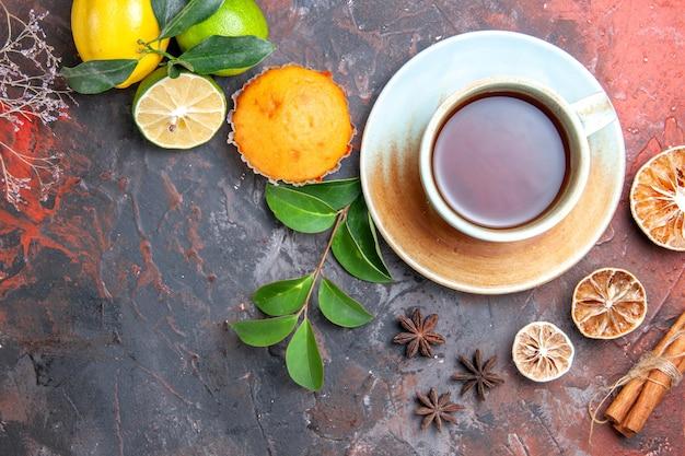 Nahaufnahme von oben eine tasse tee cupcake eine tasse schwarzen tee zitrone sternanis zimtblätter zweige