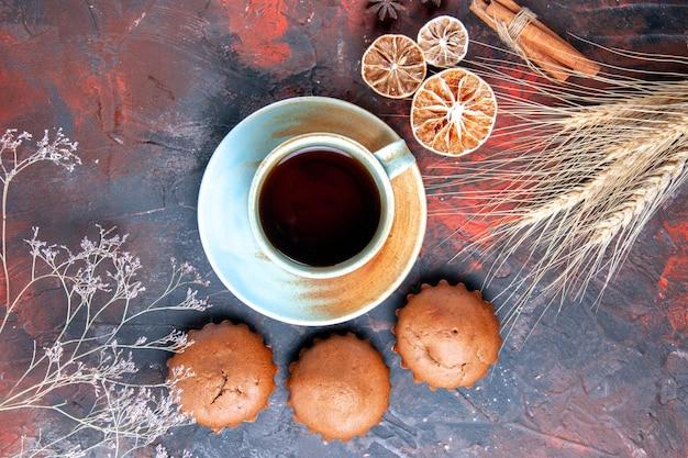 Nahaufnahme von oben eine tasse tee cupcakes eine tasse tee mit süßigkeiten zimt zitrone weizenähren