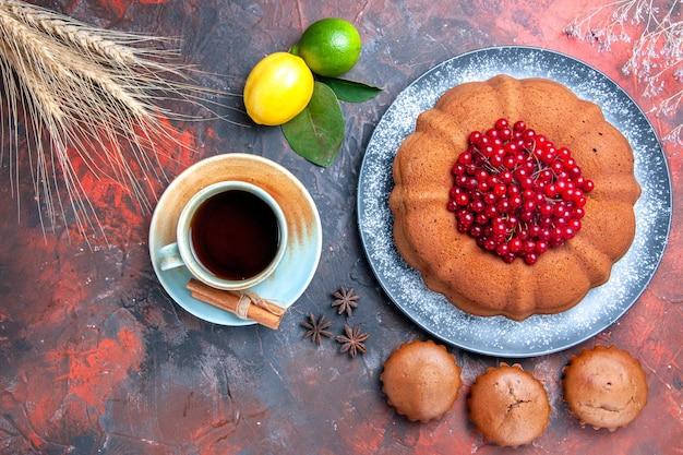 Nahaufnahme von oben eine tasse tee eine tasse tee cupcakes kuchen mit beeren zitrone und limette