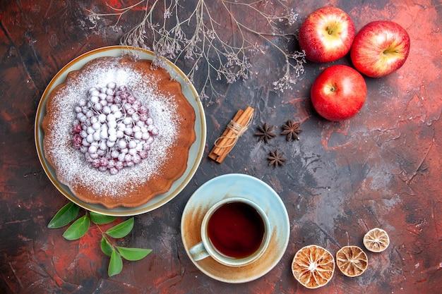 Nahaufnahme von oben eine tasse tee eine tasse tee einen kuchen mit beeren äpfel zitrusfrüchte sternanis